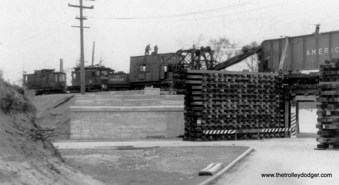 "The Evanston embankment under construction. Brian M. Hicks says this is ""the intersection of Lincoln and Ridge looking North in 1930."" According to www.chicago-l.org: ""The Purple Line shuttle is the suburban portion of the Northwestern Elevated Railroad, which opened an extension from Wilson Avenue in Chicago to Central Street, Evanston in 1908. In 1912, the line was extended to its current terminus at Linden Avenue, Wilmette. The extension opened as a ground-level line, but was elevated in sections over several decades. Of the portion of the extension now on the Purple Line, the section from Howard to University Place was elevated in 1908-10 and the remaining portion to Isabella Avenue on the Evanston-Wilmette city limits was raised in 1928-31. Unlike most parts of the ""L"", the Purple Line is elevated on a solid-fill embankment with concrete retaining walls."" (George Trapp Collection)"
