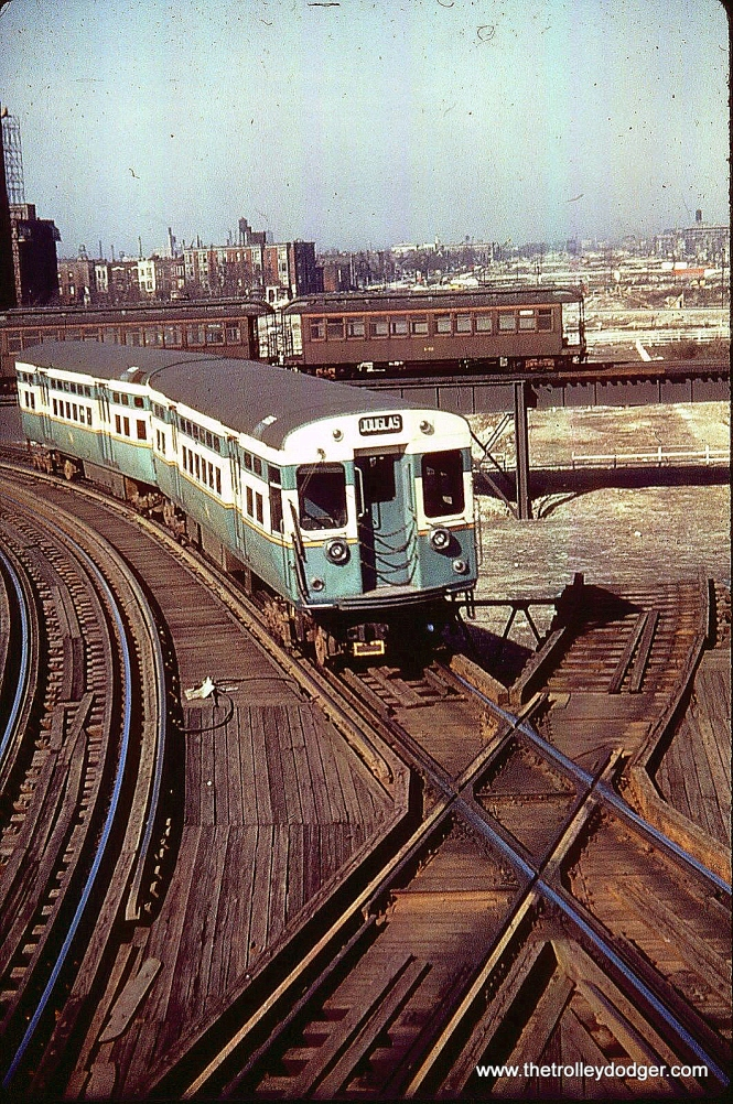 "This 1954 picture, taken from Marshfield Junction, shows the Douglas Park ""L"" in transition. The 6000s in the foreground are on the old Met ""L"" alignment, while the train in the background is on a new portion of structure, allowing a direct connection to the Logan Square portion to the north. In turn, a new connection was built allowing Douglas trains to proceed downtown over the Lake Street ""L"", which is the alignment now used once again by today's CTA Pink Line. Andre Kristopans: ""In the shot of old and new at Marshfield Jct, the 6000 is a regular Douglas train, while the woods on the connector are a work train. There was never service simultaneously on both routings."""