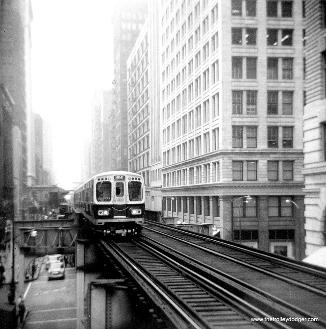 "CTA 2003-4 and 2001-2 on demonstration runs on the Wabash leg of the Loop ""L"" in 1964. This was the first series of rapid transit cars to come with air conditioning as standard equipment, something we take for granted today. Unfortunately, the AC was underpowered for the job it had to do, and the ceiling-mounted units tended to drip water on people. (George Trapp Photo)"