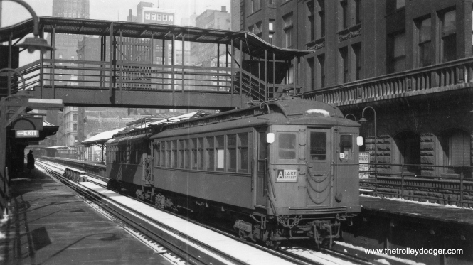 "A two-car Lake Street ""A"" train (one car is numbered 1708) on the Loop ""L"". Not sure of the exact location, but as you can see in back, this is an area where there was a continuous platform connection stations. This allowed for more trains to stop at the same time, and was likely the inspiration for the continuous platforms in Chicago's downtown subways. Myron Moyano adds, ""Car 1708 under the Lake Street section is at Madison and Wells."" (George Trapp Collection)"