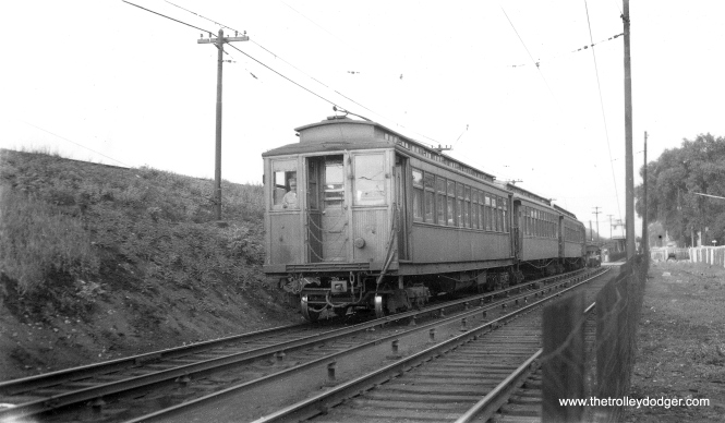 "Here, we see some Met cars in service on the Lake Street ""L"". In the days when the outer portion ran on the ground, there was a short stretch just west of Harlem Avenue, which is what we see here. There was actually a station just west of Harlem, which was not used very much, compared to the one at Harlem and Marion. Wood cars last ran on Lake on July 5, 1954. In 1962, the nearby embankment was expanded by CTA to create a new yard. (Joe L. Diaz Photo, George Trapp Collection)"