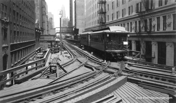 This picture was taken at Wells and Van Buren, and shows the old connection between the Met lines and the Loop. The Insurance Exchange building is at right. In 1955, this connection was replaced by one that went right through the old Wells Street Terminal, last used by CA&E trains in 1953 (and CTA in 1951). The terminal can be seen in this picture on the left hand side, where there is a walkway connecting it to the Quincy and Wells station. Once the Congress median line opened in 1958, no such connections were needed, and they were removed by 1964. (Joe L. Diaz Photo, George Trapp Collection)