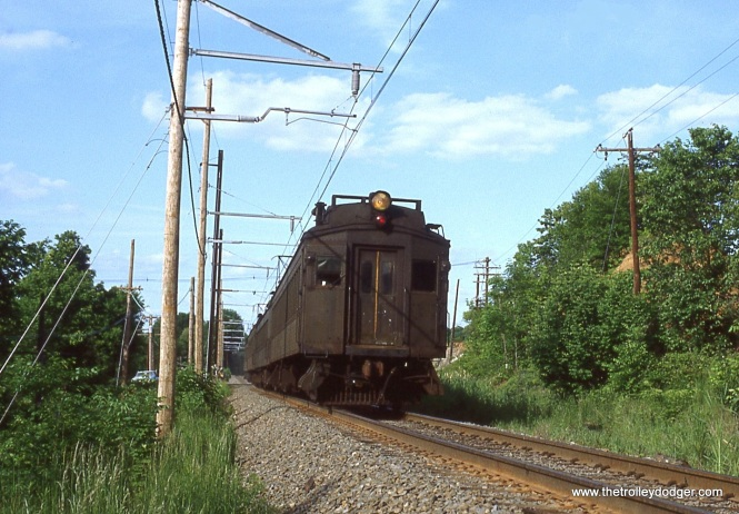 NJ Transit's Gladstone Branch took on the appearance of an Interurban railroad once it reached the open country side of Somerset County New Jersey. Close head ways, fast running, wooden catenary poles, and 1930's era MU equipment combined to create that Interurban look. This photo shows clearly the wooden catenary poles as a fast running Gladstone bound train of Ex-DL&W DC electric MU cars fly down the track near Bernardsville, NJ on June 2, 1983. (Kenneth Gear Photo)