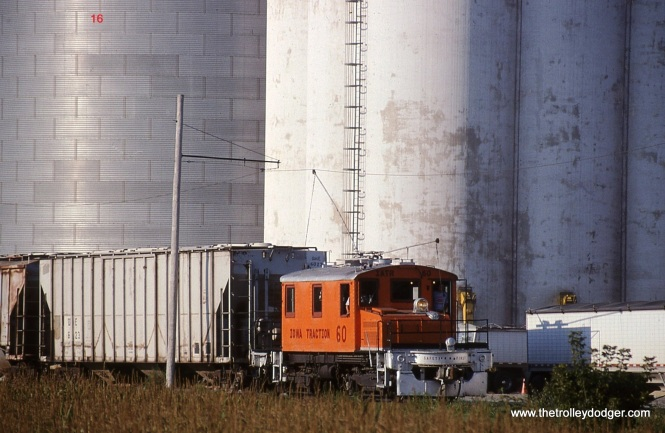 16. Iowa Traction Steeplecab # 60 is dwarfed by the silos at the AGP soybean processing plant. Mason City, IA. 8/22/06