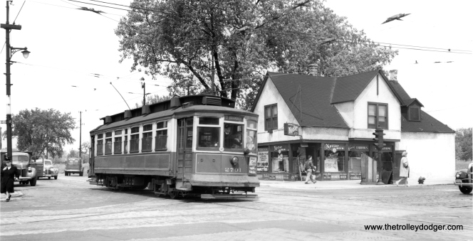 "The photo caption reads, ""The open fields behind car 2701 notwithstanding, the corner of 79th and State was a busy transfer point. This eastbound 79th Street car clatters over the CSL tracks on State."" (Joe L. Diaz Photo)"