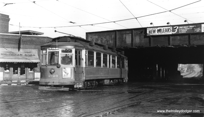 "The caption on this photo reads, ""Westbound car 2623 passes under the Illinois Central main line at 75th and South Chicago Avenue, over the diagonal tracks of the busy South Chicago line."" Bill Shapotkin notes, ""Indeed, this car is on 75th St and has just x/o UNDER the IC. The car is W/B (note platform of IC's Grand Crossing station at left atop embankment)."" (Joe L. Diaz Photo)"