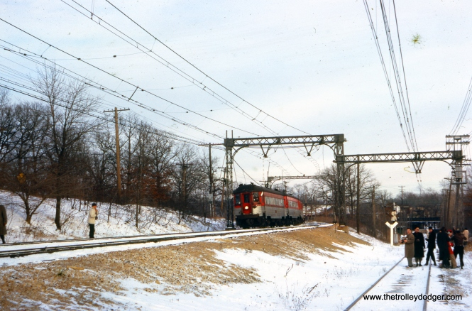 "A photo stop on the same January 13, 1963 fantrip. Perhaps one of our keen-eyed readers can help identify the location. Don's Rail Photos says, ""774 was built by Standard Steel Car Co in 1930, It was rebuilt as Silverliner on May 9, 1950."" Joey Morrow writes: ""NSL 774 is west of Green Bay Jct. The line to the west leads to the Highwood shops and offices. In the distance you can see the bridge that is currently used by the Metra UP-N. You can still see where the NSL once ran under the bridge. The line to the east leads to The Lake Bluff station just across the street out of the shot. Not totally sure if the cement that once held the catenary supports is still there or not, but the telephone POLES behind the camera man are still there."" (J. W. Vigrass Photo)"