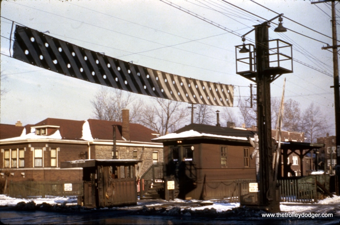 "When I got this slide, it was identified as being a station on the Garfield Park ""L"". However, I did some further research, and it is actually the old Austin Boulevard stop on the Douglas Park line. The house and apartment buildings in the background are still there. The Douglas branch was cut back to 54th Avenue in 1952 and the former right-of-way is now used for parking. Locals still call it the ""L"" Strip."