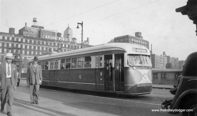 "CSL 7024 is westbound on Madison just west of the Chicago River in this September 8, 1937 view. The photo caption describes this as a ""noiseless streetcar,"" with magnetic air brakes and rubber cushioned wheels."