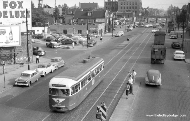 "CTA 4002 is shown heading north on route 49 - Western on July 14, 1953. The photographer was up on the Logan Square ""L"" platform. The people at right are waiting for a southbound car at a safety island. In the distance, we see what was then the Bloomingdale freight spur of the Milwaukee Road, but is now part of the 606 Trail. Jim Huffman adds, ""Photo #525. ""CTA 4002 is shown heading north on route 49 – Western on July 14, 1953"", I feel is incorrect. 1. There is a 1955 Chevrolet on the left, precludes 1953. 2. 1-Man, Pre-War PCC were assigned in June 1955 (as well as 1-Man Post-Wars), prior to that Western used 2-Man Post-War PCCs only. Went Bus in June 1956. 3. People standing on the safety island are waiting at the end for the front door boarding of an 1-man car. Prior to 1-Man cars, they waited at the other end for the rear doors. 4. Although there is no proof, the 55 Chev looks somewhat used, I would say this is a 1956 photo."""