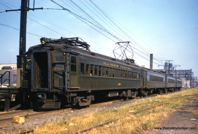 "Illinois Central Electric car 1210 heads up a Randolph St. Express on September 9, 1959. Don's Rail Photos adds, ""1100 thru 1239 were built by Pullman in 1929. 1198 went to Illinois Railway Museum in 1972."" (Clark Frazier Photo) Andre Kristopans: ""IC 1210 – arriving at 91st/South Chicago. Tracks on right were B&O. Note trailers were always at the NORTH end of an IC Electric train, as only a trailer would fit under the old South Water St entrance to Randolph St Station, so in order to use the full track length, trailers always had to lead north."" Daniel Gornstein adds, ""I'm not sure if anyone else has replied on the IC 91st St. photo yet, but the unquestionable answer is on the catenary pole. If you look closely on the macro view you will see, arranged vertically, this: ""SC4-33,"" meaning South Chicago Subdistrict, located at MP 4.33. The 2 branches used to have independent MP's, but are now shown on Engineering Dept. files as the same distance to South Water St., as the Univ. Pk. mainline does. To the photographer's rear is 91st St. and in the distance, just north of 90th St., is NB signal 420, or approx. MP 4.2. IRM's operable ""Suburban Unit"" is motor 1198, as noted, and trailer 1380."""