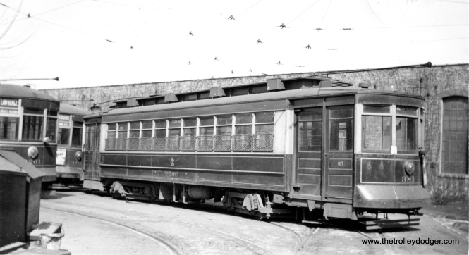 "CSL 381. Andre Kristopans: ""Probably somewhere in Devon Carbarn yard. Lawrence and Broadway/Wabash both ran out of there."" George Trapp adds, ""I am pretty sure the location is at the Devon Depot, the east end of the South open yard, the ladder track curves out into Schreiber Avenue behind the photographer. Car 381 is signed for Cottage Grove-Broadway TR#1. Car 3201 to it's left is signed for Lawrence which operated out of Devon in the 1930's, it is one of the two original MU cars, 3200-3201 with 4 motors. These cars operated on Broadway during the daytime as two man cars and as night cars on Lawrence as one man. The car barn structure also looks like Devon Depot."""