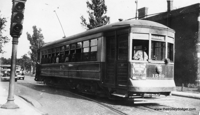 "It's not easy to determine just where this picture of CSL 1589 was taken on August 4, 1934. The car is signed for Irving Park and Neenah, and with the track configuration, you would expect we are at the east end of the Irving Park line. However, according to my CSL track maps, the crossover was just west of Broadway. If so, that doesn't explain the traffic signal in the picture. Perhaps Irving Park cars turned back just east of Broadway? (Earl W. McLaughlin Photo) Andre Kristopans: ""More likely Irving and Clark. Note cemetery behind car."""