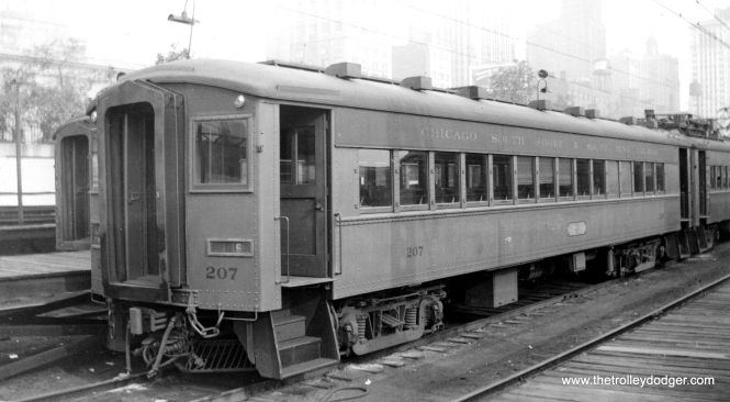 "Caption: ""Chicago, South Shore and South Bend trailer 207. Although this car has no motors, it has controls, and can be used as (the) head car in (a) train. These trains make the 90 miles to South Bend in 2 hours and go over 100 to keep up schedule, and they go through city streets in several cities, among them Gary. They use tracks of the Illinois Central out and in Chicago. Builder- Pullman."""
