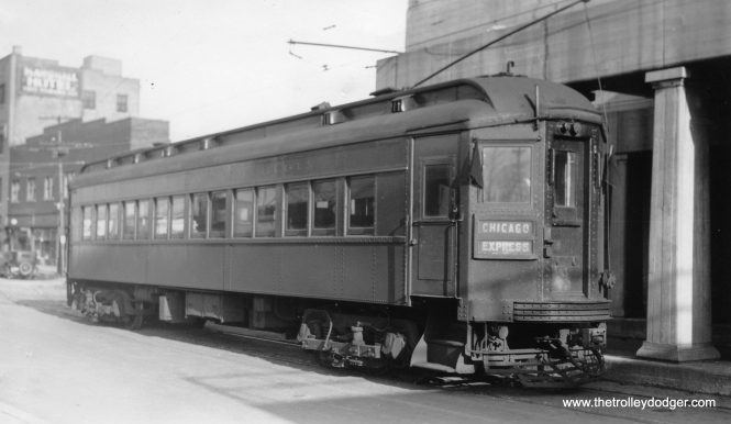 "Chicago, Aurora & Elgin car 107 under trolley wire in downtown Aurora in 1936. Within a short period of time, the street running in Aurora was eliminated and replaced by a new terminal with private right-of-way. Don's Rail Photos: ""107 was built by Stephenson in 1903. It was wrecked in 1914 and rebuilt as an express trailer. It was retired in 1937."" I'm not sure if this is really car 107 (as the photo says it is), since this car looks like it can run under its own power, which an express trailer could not do. Andre Kristopans: ""CAE car in Aurora – probably 407. 107 was a woodie to begin with!"" Don's Rail Photos says, ""407 was built by Pullman in 1923."" Bill Shapotkin adds, ""This pic is indeed in Broadway at the CB&Q overcrossing (just south of Benson). When the streetcars quit in Aurora, the car tracks (which had at one time gone under the CB&Q) were cut-back to this point. The view looks N/E."""