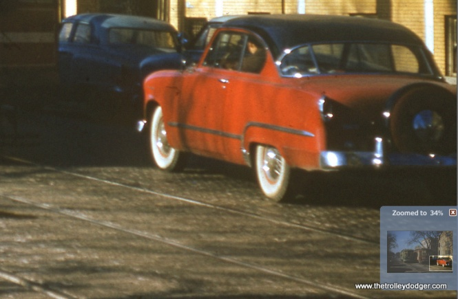 "I'm having difficulty identifying this car. But note it has a ""continental"" spare tire, implying it is not one of the cheaper models. The newest it could be is a 1954. The 1955 models wouldn't have been on the market until some months after streetcars quit on Lake Street. So far, my best guess is this may be a 1953 Dodge Coronet. Gary Kleinedler: I believe that the CTA 1782 & 1774 photo shows a 1953 Dodge Coronet Diplomat 2-door hardtop. All 1952 Dodge models had separate, bolted-on rear fenders; the photo shows a straight fender sideline. The 1953 Coronet series was the top trim line (Meadowbrook--Coronet; Wayfarer models were discontinued after 1952), and a Coronet 2-door hardtop would have a three-piece wraparound rear window and V-8 Hemi engine. The 1954 Dodge Coronet (and new top-line Royal) models had the model name in script on the rear fenders, which doesn't seem to be present in the photo. A Continental spare wheel kit and wire wheels (which appear to be present) were both offered as factory options in 1953. I took the above info from the Standard Catalog of American Cars, 1946-1974, John Gunnel, ed."