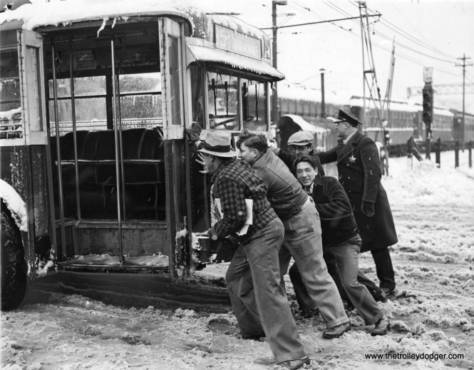 "April Blizzard Ripples Chicago Traffic (April 7, 1938): Chicago- Passengers, bystanders and a policeman pushing a Chicago trolley bus so it could get traction on a slippery street, after the city suffered a record April snowfall of more than 7 inches of wet snow that crippled traffic. (Editor's note: This picture was taken on Central Avenue, where CSL route 85 crossed the CRT's Lake Street ""L"" at ground level. You can see several CRT cars in the background. As far as I know, this was the only place in Chicago where a trolley bus crossed a trolley ""L"". The bus was heading south.)"