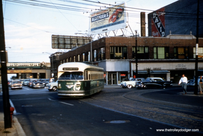 "On august 21, 1956, PCC 7215 turns from Broadway onto Devon, as a northbound route 36 car with the North Side ""L"" in the background. (Joseph M. Canfield Photo)"