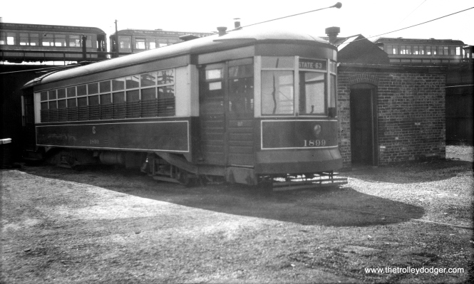 "This picture is a bit of a mystery. Although CSL 1899 says it is destined for 63rd and State, that is not this location, since we see the ""L"" in the background. Sandy Terman: ""The photo of flexible 1899 I believe was taken in the lower yard north of west shops just north of Lake street.The trains above I think were actually Lake Street. the 1899 may have been pulled out of service from the State-Lake route according to the destination sign."" That's a pretty good theory, and backing it up, you can see trolley poles on some of the ""L"" cars in the picture. If Mr. Terman is right, those cars are being stored on a third track on the Lake line, which did not have a ""proper"" yard at the end of the line until after the 1962 elevation."