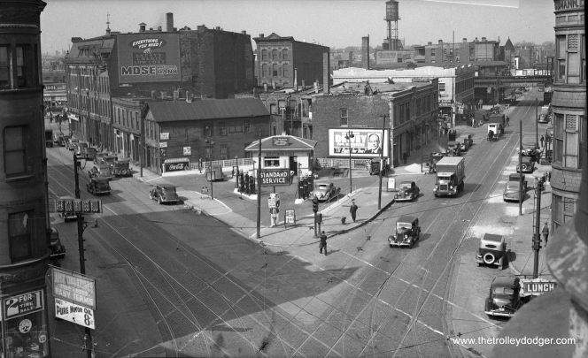 "Clybourn (left) and Halsted (right) in 1938. There are no streetcars present, but plenty of tracks. In the background, we see part of the Northside ""L"", generally called the ""triple curve."" The State Street subway had not yet been built when this picture was taken, but a station at North and Clybourn would eventually replace the one here on the ""L"". This section of line is still used today by Brown and Purple Line trains, and has not been straightened out."