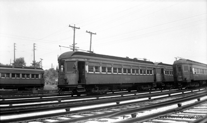 "CA&E wood car 138 at the Wheaton Yard on July 3, 1949. Don's Rail Photos says, ""138 was built by American Car Co in March 1910, #844, as C&ME 138. It was rebuilt in 1914 and no retired date."" This was one of several cars leased from the North Shore Line in 1936 and purchased from them a decade later. Ironically, this made them the last passenger cars bought by CA&E. They were considered surplus after service was cut back to Forest Park in 1953 and were scrapped shortly thereafter."