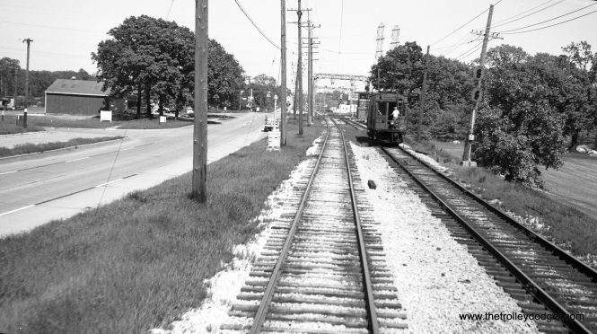 Richard H. Young took this picture on June 2, 1960 from the back of a moving North Shore car somewhere near Mundelein. We see a line car at work on the other track. One of our regular readers says that we are looking east toward South Upton tower, with Rt. 176 at left (north).