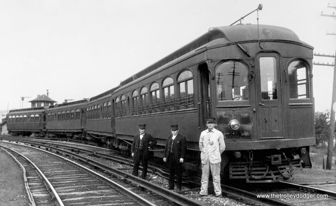 A train of the first cars with just the top of the old dispatcher tower in the background.