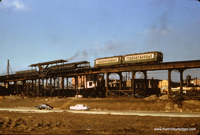 "This photo shows the Kilbourn station on the Garfield Park ""L"" around 1954. By then, the station had been closed, and the stairways removed, in order to reduce running time due to the slow 2.5 mile temporary trackage at ground level east of Sacramento. The two-car train of CTA 4000s is about to cross the Congress Expressway, but the highway does not appear to be open yet. The ""L"" tracks were higher than normal at this location to cross railroad tracks just west of here. The line was relocated into the expressway median in 1958."