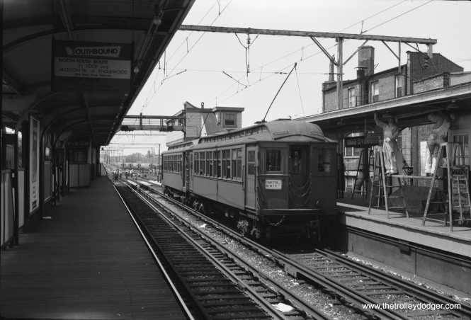 "A northbound two-car Evanston shuttle train is held up momentarily at Howard in the 1950s, as track work is going on up ahead. The rear car is 1766. Don's Rail Photos says, ""1756 thru 1768 were built by Jewett Car in 1903 as Northwestern Elevated Railway 756 thru 768. They were renumbered 1756 thru 1768 in 1913 and became CRT 1756 thru 1768 in 1923."" Wood cars last ran on Evanston in 1957. Notice that the station is also being painted."