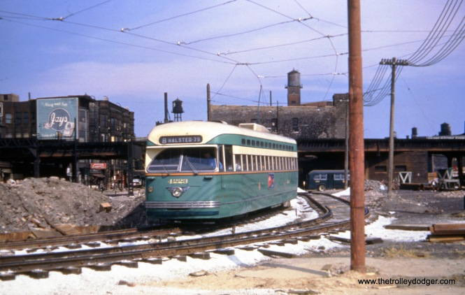 "CTA Pullman-built PCC 4223 on a shoo-fly at Halsted and Congress circa 1952. The Congress expressway was under construction, and the first thing built were the bridges. That is the Garfield Park ""L"" in the background, which continued to operate until June 1958. The temporary trackage in Van Buren Street was a short distance west of here. We are facing north. Those lines on the car are shadows from nearby telephone wires."