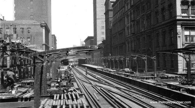 "When I received this picture, it was identified only as being on the Wells Street leg of the Loop ""L"". However, the construction work shown identifies it as Quincy and Wells, circa 1926-27. The ""L"" platforms are being extended with metal canopies, while work at left is underway on the Wells Street Terminal, which had an impressive three-story facade designed by Chicago Rapid Transit Company staff architect Arthur U. Gerber. We are facing north."