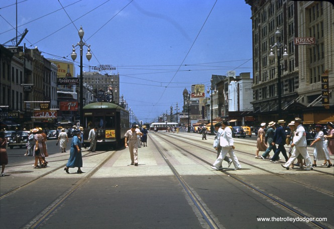 "This remarkable Kodachrome image was taken on Canal Street in New Orleans on June 19, 1940. It was shot on size 828 film, which has an image area of 28x40mm, about 30% larger than 35mm. (828 film, which Kodak introduced in the late 1930s, was essentially 35mm film without sprocket holes, but with a paper backing like other roll film formats.) One of our regular readers writes, ""The 4 tracks were taken out about 1948 when a number of the car lines that operated off of Canal were converted to trolley bus."" The location is the intersection of Canal and St. Charles. Car 444 is looping at the end of the St. Charles route and will be turning to the left in the picture. WSMB (now WWWL) was an AM radio station at 1350 on the dial. Its old call letters reflect its original ownership by the Saenger theater chain and Maison Blanche department store. Its studios were located in the Maison Blanche department store building at right, now the Ritz-Carlton hotel. The Saenger Theatre, another local landmark, is also on the right side of the picture. In the days before air conditioning, men used to wear white suits, as you see here, since white reflects more heat than darker clothing. When this picture was taken, France had just fallen to Nazi Germany. The US did not enter World War II directly until 18 months later."
