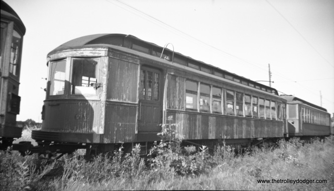 "Chicago Lake Shore & South Bend Ry. (predecessor of the South Shore Line) car 68 at an unknown location near a wooden Chicago ""L"" car. This photo is a real mystery, since, as far as I know, this car has not been preserved (although car 73 is being restored). Joe writes: ""Car 68 is Lake Shore Electric, not CLS&SB, built by Brill in 1903. The car behind it is one of the LSE's Barney & Smith interurban cars."" That clears up the mystery. The information that came with this negative was incorrect."