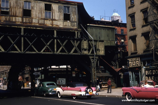 Here is a very interesting streetscape. It shows one of the old Third Avenue El stations in the Bowery, Manhattan in 1955, possibly after the line closed on May 12. Those two convertibles are Fords.