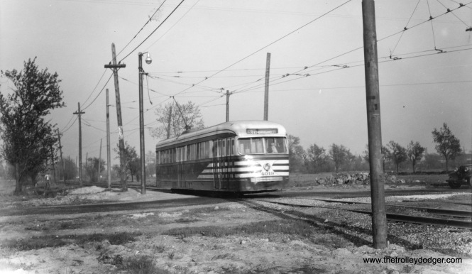 "CTA 4019 is westbound on private right-of-way on 63rd Place, near the Narragansett loop. You would hardly recognize the location today, as it is in the middle of a quiet residential neighborhood. This prewar PCC, in ""tiger stripes,"" still has a CSL logo on it."