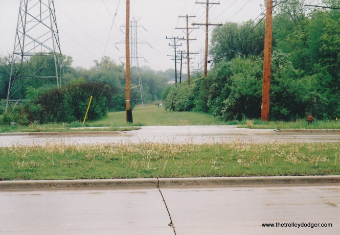 Other sections of the abandoned Hales Corners line r.o.w. are still very visible. Here you see the crossing of W. Layton Ave. looking south. In the 1930's a line was built southeast from this point for transporting work crews to the abuilding village of Greendale. The line was dismantled upon completion of construction.