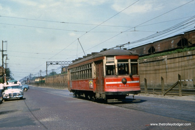 "CTA one-man streetcar 3144 heads east on Route 16 - Lake Street somewhere between Laramie and Pine Street, while a two-car train of 400-series ""L"" cars runs at ground level parallel to the streetcar. The time must be near the end of red car service here, which was May 30, 1954, as that is a 1953 or 1954 Cadillac at left. The C&NW signal tower on the embankment is still there today, at about Pine Street, which is where streetcars crossed the ""L"" to run north of the embankment for a few blocks before terminating at Austin Boulevard, the city limits."