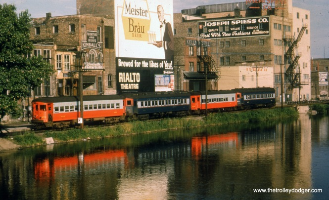 "A classic view of the CA&E in Elgin, with a beautiful reflection from the Fox River. A sign advertises the Rialto Theatre, which burned down in 1956. The fiim being advertised, The Big Sky starring Kirk Douglas, was released in August 1952, which is most likely when this picture was taken. George Foelschow adds: ""Four cars at the Elgin terminal. This must be a fantrip, as single cars were the rule on the Elgin branch, except for weekday rush hours and Sunday afternoons for visitors to the Elgin State Hospital."""