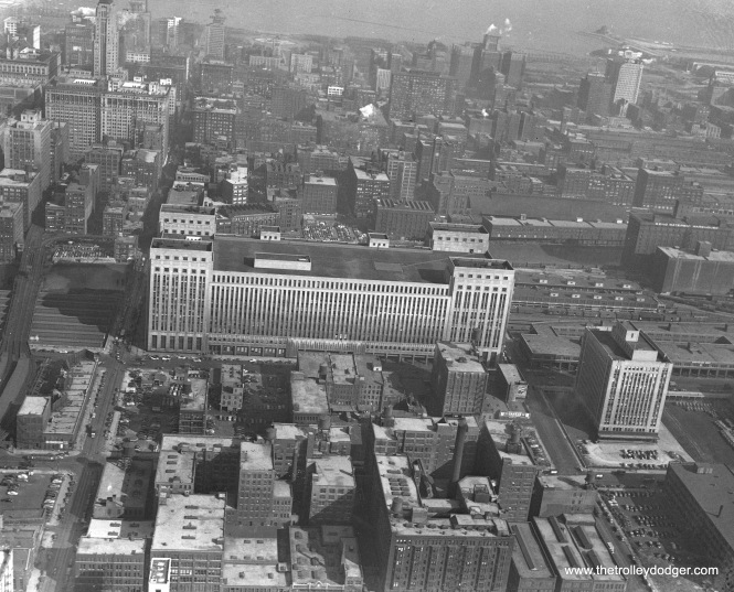 "This aerial view shows the old Main Chicago Post Office and the near west side in 1946, before work started on building the Congress Expressway (now Eisenhower), which now runs right through the center of the building. That will give you an idea of just what a massive project this was. The old Metropolitan ""L"", parts of which were displaced by the highway, has already curved off to the left, where it can be seen crossing the Union Station train sheds. Two side-by-side bridges carried the four tracks over the Chicago River. Then, tracks split, one part going to the Wells Street Terminal, the other continuing to a connection with the Loop structure at Wells and Van Buren. Now, the CTA Blue Line subway goes underneath the post office and river."