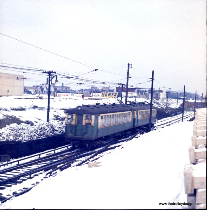 """A two-car train of CTA 4000s at the west end of the Lake Street """"L"""" in Forest Park. This picture was probably taken circa 1961-62, since you can see that at right, work is already underway on expanding the embankment to create space for a rail yard. On October 28, 1962, the out end of Lake was relocated to the C&NW embankment at left."""
