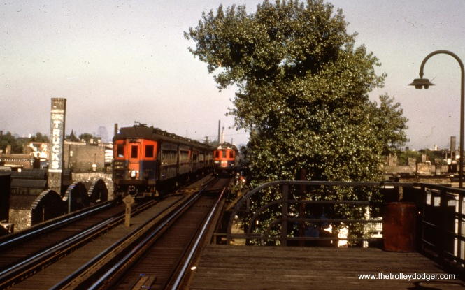 "Two ""Roarin' Elgin"" trains pass on the Garfield Park ""L"". Cliff W. says we are ""looking east from Pulaski with the single crossover just east of the station visible."""
