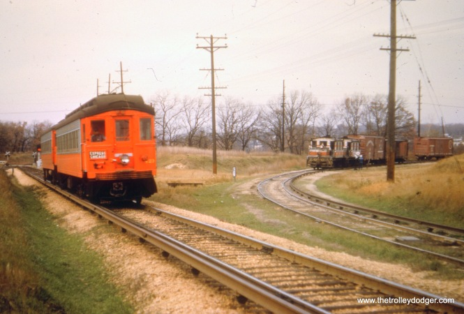 "CA&E 423 (plus one) head east towards Chicago, while a freight is on a nearby spur line. Bill Shaptokin says this and the next two pictures are ""at Renwick -- interchange with the MILW south of Elgin."""