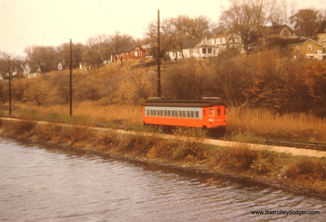 "A single car near the Fox River. Bill Shapotkin: ""This pic is in Batavia (NOT Aurora). Shot is between Batavia Station and Glenwood Park."" On the other hand, George Foelschow writes, ""This is most assuredly on the south side of Elgin, near the point of changeover between trolley and third rail. Not for nothing is Elgin, my hometown, called ""The Bluff City"", also the name of the municipal cemetery, served at one time by Grove Avenue streetcars."""