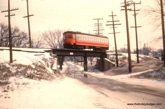 "Not sure where this curved-sided CA&E car is. Cliff W.: ""The single Saint Louis car going over the bridge is passing over Liberty Street in Wheaton directly north of the shops and approaching the bridge over the C&NW on the Elgin branch. If you look very closely at the far right of the picture you can see a CA&E car sitting in the yard."" Bill Shapotkin: ""This car is x/o Liberty Drive in Wheaton (on the Elgin Branch): (View looks E/B on Liberty)."""