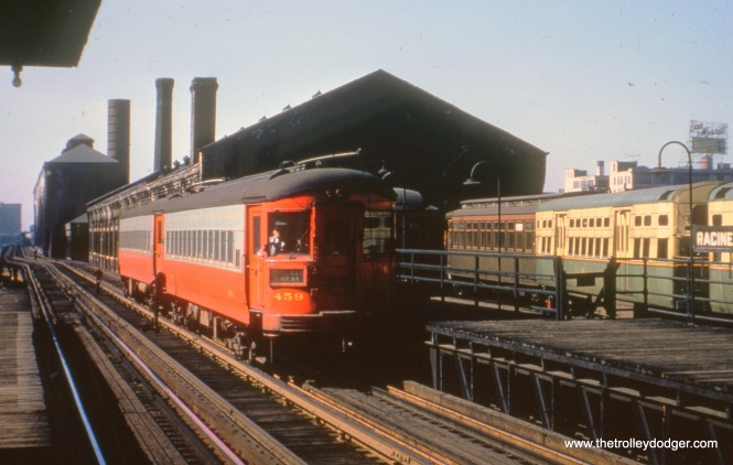 "Racine station on the old Met main line, with the Throop Street Shops in the background. This picture was taken sometime between 1950 and 1953, as there are some ""flat door"" 6000s present (along with Met car 2880)."