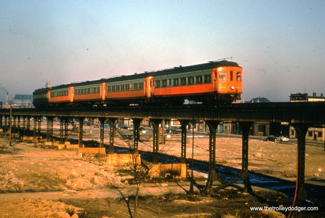 """A train of CA&E woods, headed up by 302, goes up the ramp to cross over the C&NW/PRR right-of-way at Rockwell. The """"L"""" was raised up when the line it crossed was elevated onto an embankment. That explains why there are brick bases for some of the """"L"""" support columns."""