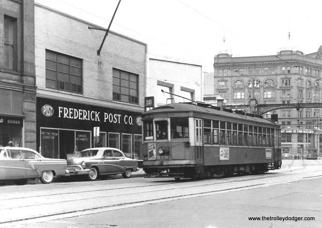 "The late Ernie Maragos of Racine, Wisconsin took this photo of Milwaukee & Suburban Transport Corp. streetcar 978 in 1957. The eastbound car has just crossed the Milwaukee River on the bridge in the background and will stop at N. Water St. about a half block out of the picture at left. The large building seen behind the 978 is the Germania Bldg. on the southwest corner of N. Plankinton Ave. and W. Wells St. The domes with what look like spears were meant to simulate German Pith helmets. Due to anti-German sentiment during WW I the owner, Henry Brumder changed the name of the building to the Brumder Bldg. Brumder was a newspaper publisher who printed German language newspapers for Milwaukee's large German population. The ""Germania"" name was restored in the 1980's and the building given a complete renovation. The publishing of newspapers had ended many years before and the former printing press area in the basement was converted to a parking garage for the 4 top executives of Security Savings & Loan Assoc. on the northeast corner of 2nd & Wisconsin (adjacent to where the North Shore city carline ended). I worked for Security S&L for almost 20 years, then went to work for the bank that bought out Security in 1997. The 978 was saved by former Milwaukee resident Al Buetschle for the Wauwatosa Kiwanis Club. When they changed their mind, ownership reverted to him. When he left Milwaukee in 1961 to pursue a job in Northern California the car went to the Mid-Continent Railway Museum in North Freedom, Wi. The group that formed the East Troy Trolley Museum in 1972 - TWERHS, The Wisconsin Electric Railway Historical Society was formed at Mid-Continent and split off in 1967. Mr. Buetschle now resides in Contra Costa County, Ca. 60 miles northeast of San Francisco."