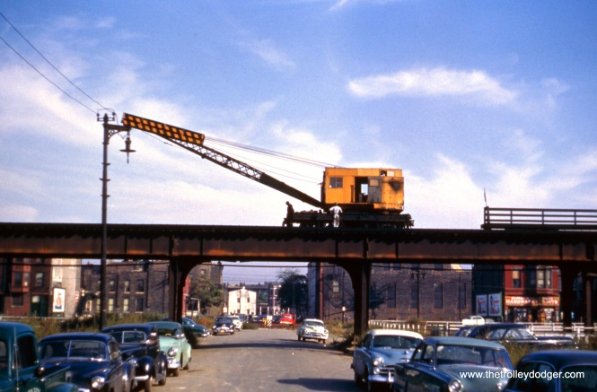 "This picture shows a CTA crane in operation on the old Metropolitan or Garfield Park ""L"" in the early 1950s. You can see how many nearby buildings have already been cleared away in order to build the Congress Expressway."