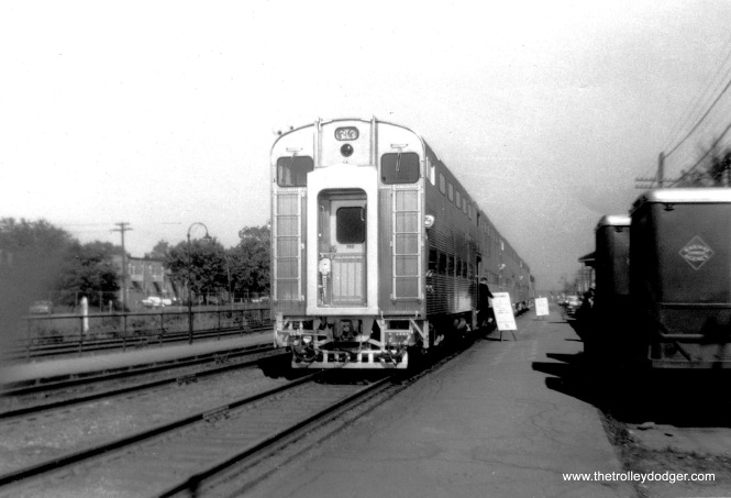 "I think what we are seeing here is new commuter rail bi-levels on display, probably the Milwaukee Road, in July 1961. The sign at left says, ""Entrance,"" implying that they wanted you to walk through the cars in one direction only. At right are some vehicles from the Railway Express Agency (REA), which delivered small packages via the railway system between 1917 and the late 1960s. It was a national monopoly formed by the federal government during the First World War."