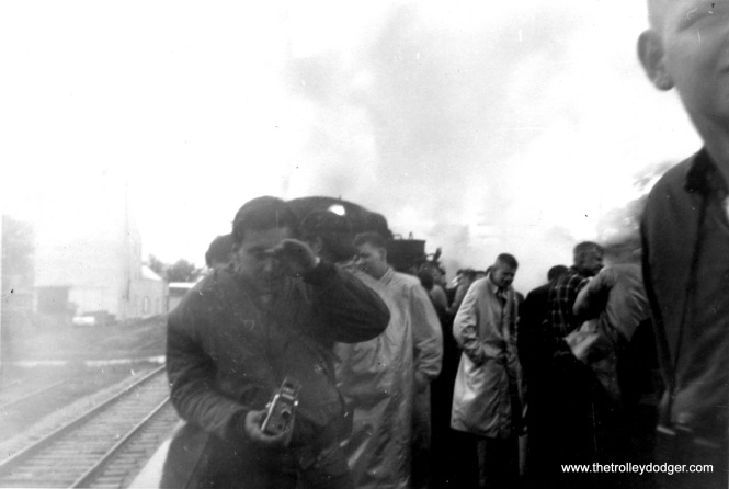 "One thing about steam... as the song goes, smoke gets in your eyes. Note the small twin-lens reflex camera this shutterbug is holding. Perhaps a grey ""Baby"" Rolleiflex, which took size 127 film? (On the other hand, Carl Lantz thinks thinks he's holding a movie camera.)"